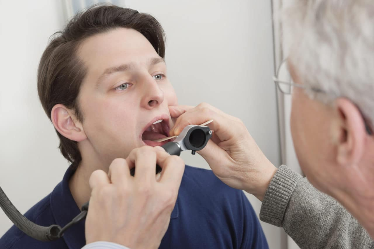 Doctor looking into patient's throat