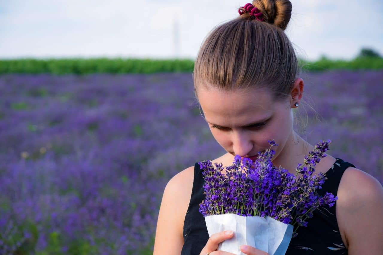 a woman smelling a bunch of lavender next to a field of lavender
