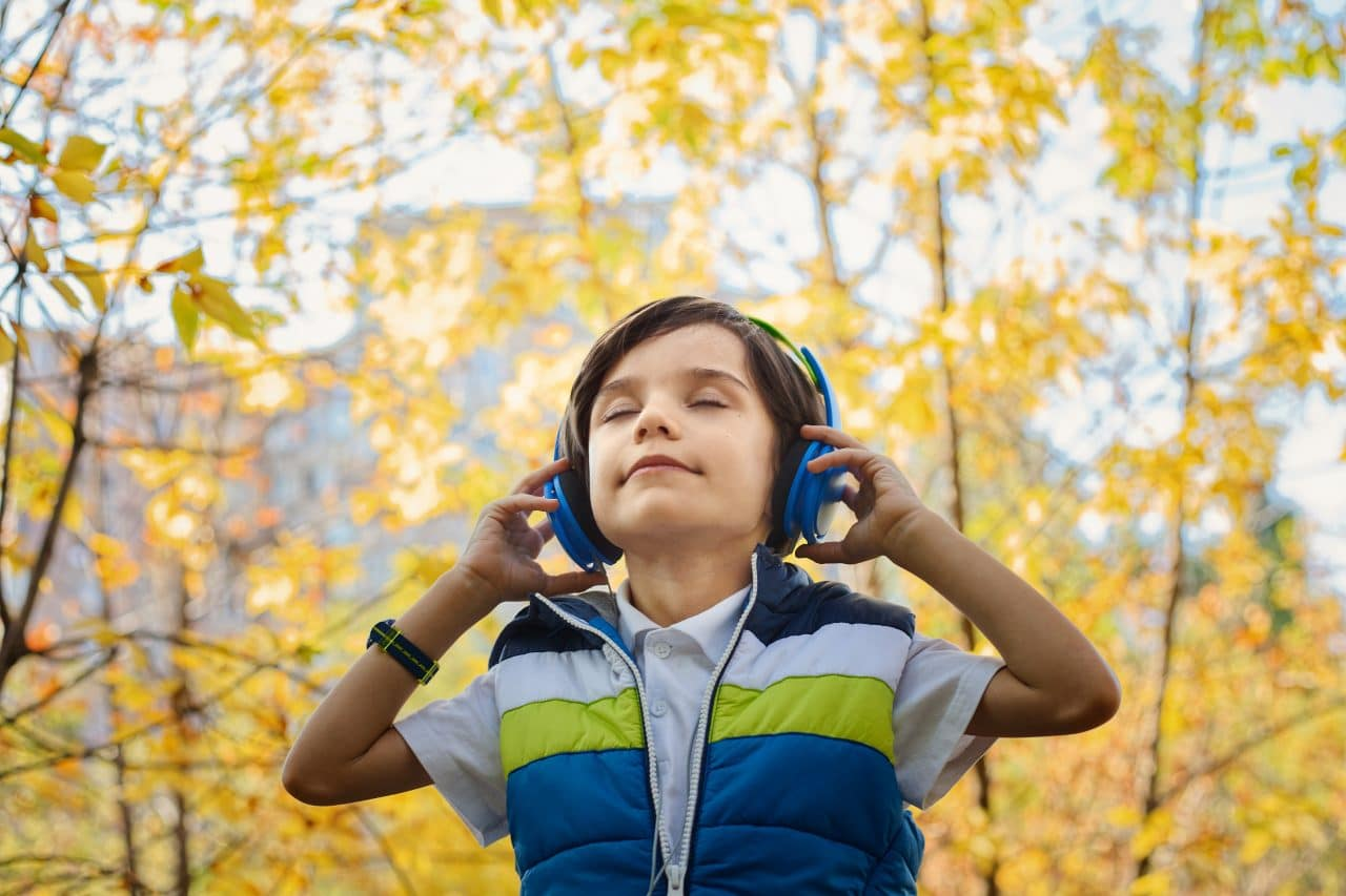 Boy with headphones on with trees in the background