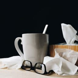 A mug, a pair of glasses and some tissues.