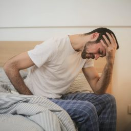 Man with a headache sits on the edge of his bed.