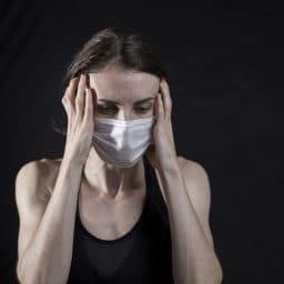 Woman wearing a mask in distress