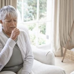Woman coughing in her living room at home.